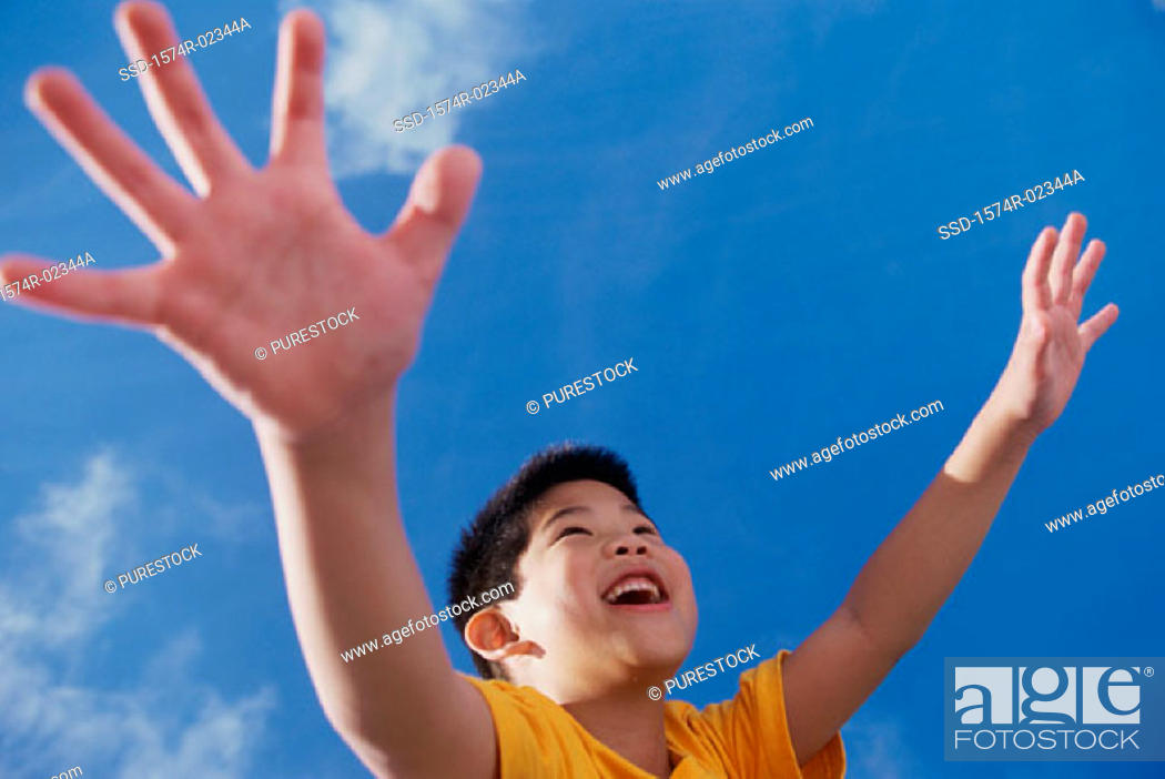 Photo de stock: Low angle view of a boy with his arms outstretched.