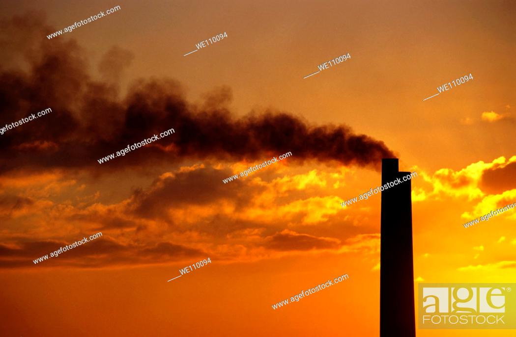 Stock Photo: Silhouetted smoking chimney at sunset, Berre, France.