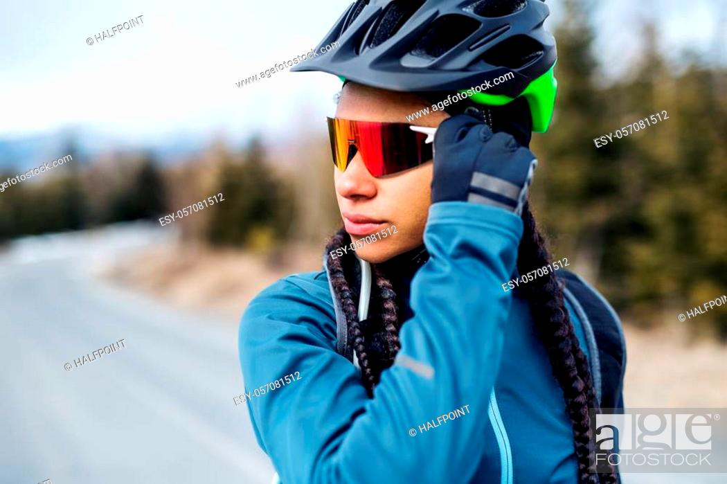 Stock Photo: Female mountain biker with sunglasses standing on road outdoors in winter.