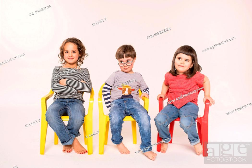 Stock Photo: Portrait of three children sitting in colourful chairs, studio shot.