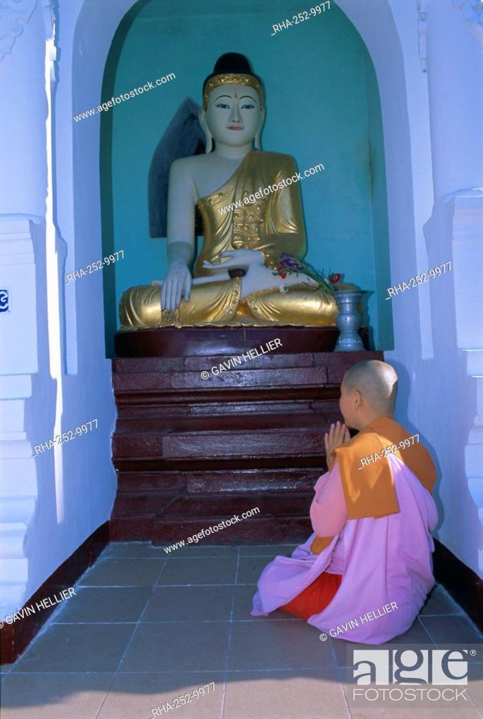 Nun and statue of the Buddha, Shwedagon Paya Shwe Dagon pagoda