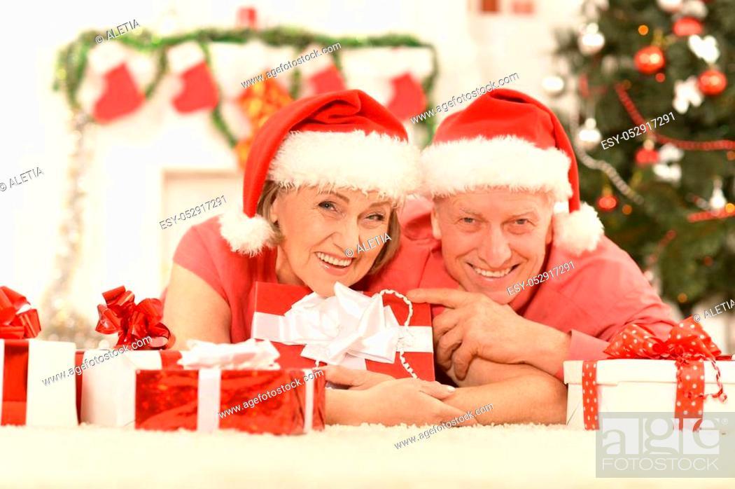 Stock Photo: Amusing old couple wearing Christmas holiday caps.
