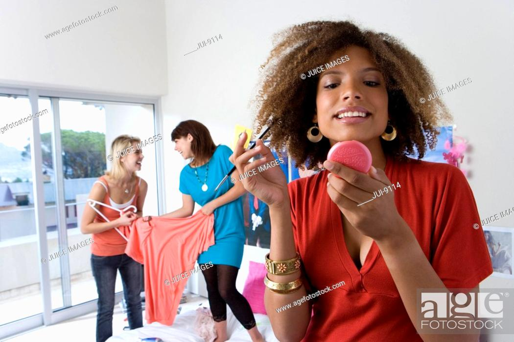 Stock Photo: Three teenage girls 15-17 in bedroom, girl applying make-up in foreground.