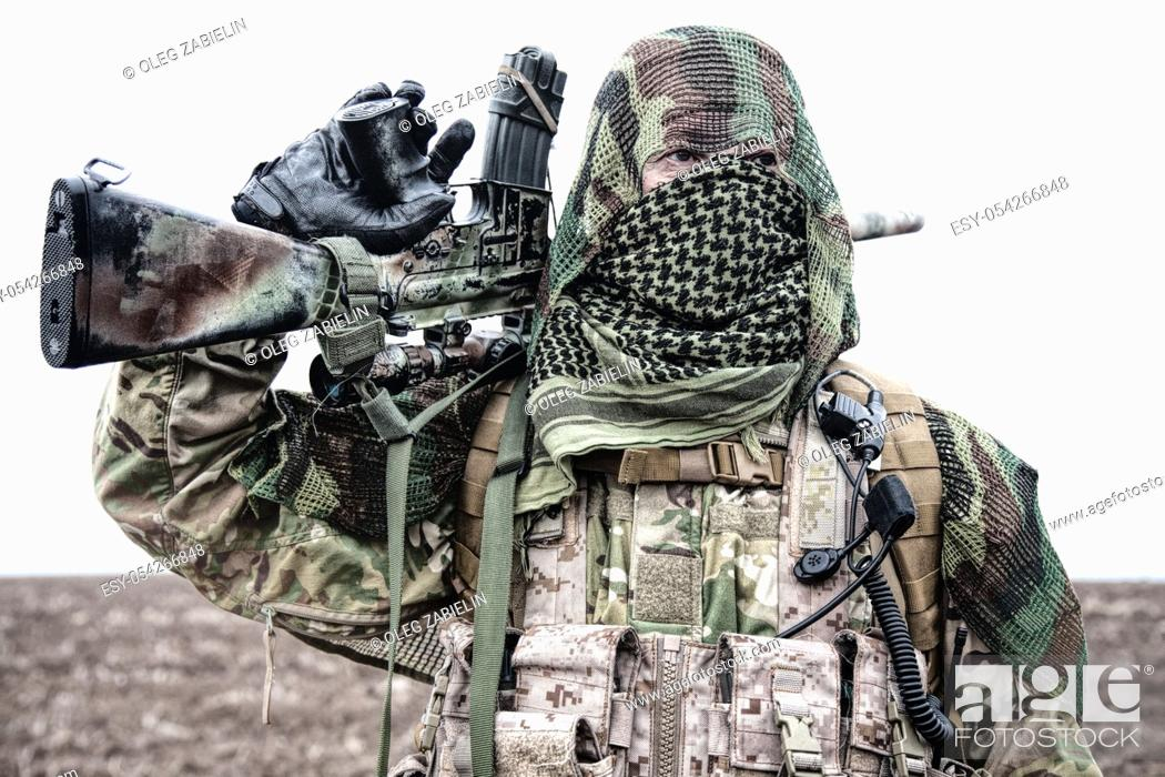 Imagen: Army marksman, airsoft player in camouflage uniform and load carrier, masking cape on head, armed service rifle with optical sight, hiding face with shemagh.
