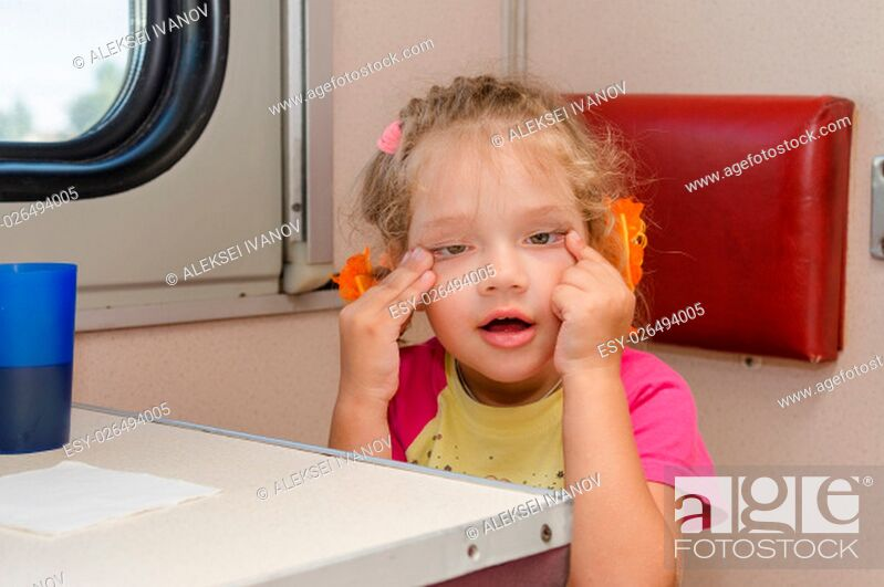 Stock Photo: Girl makes faces four years of sitting on the train at the table on the side a place reserved seat.