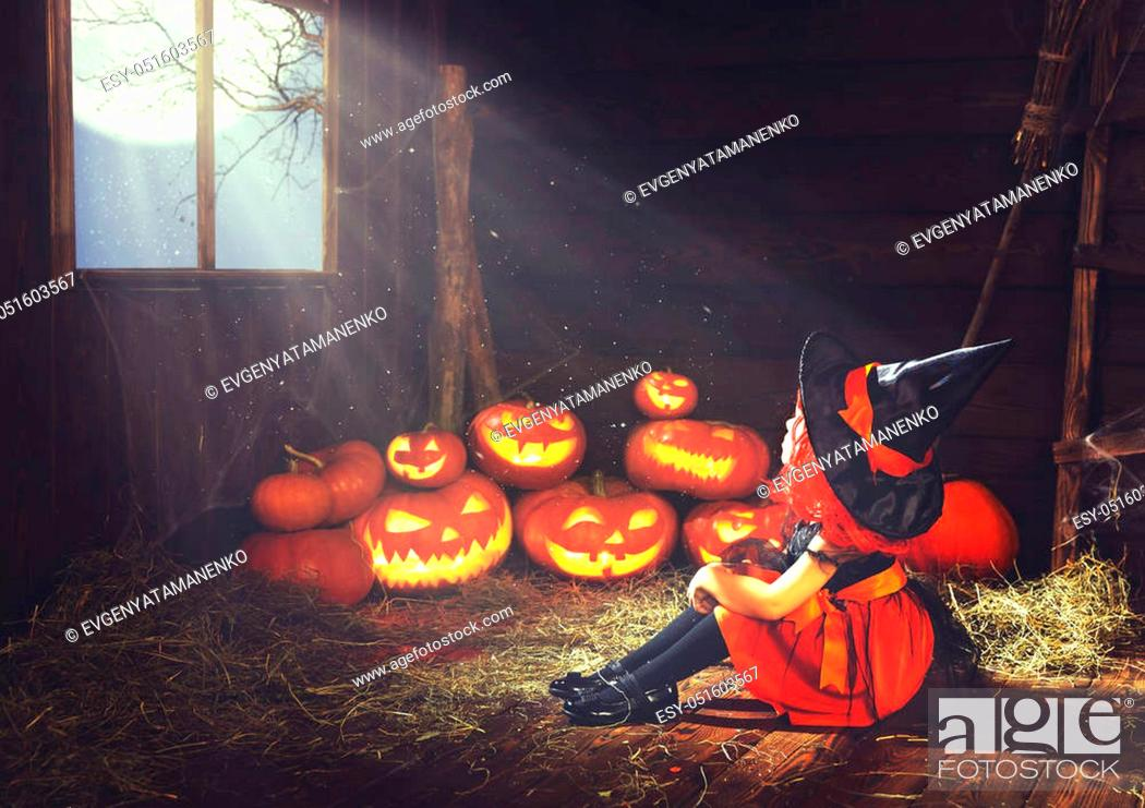 Stock Photo: Halloween. child little witch with pumpkin by the window waiting for a miracle and magic in old hut.