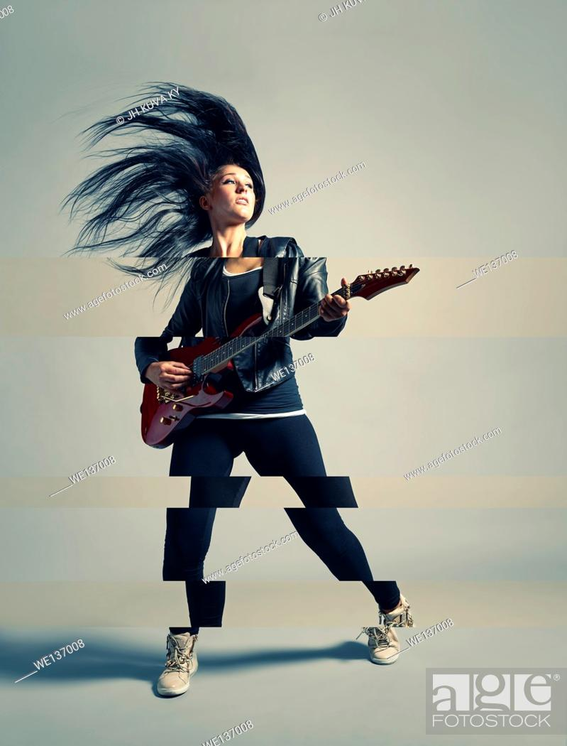 Stock Photo: Woman rocker and an electric guitar, studio shot, cross processed image.