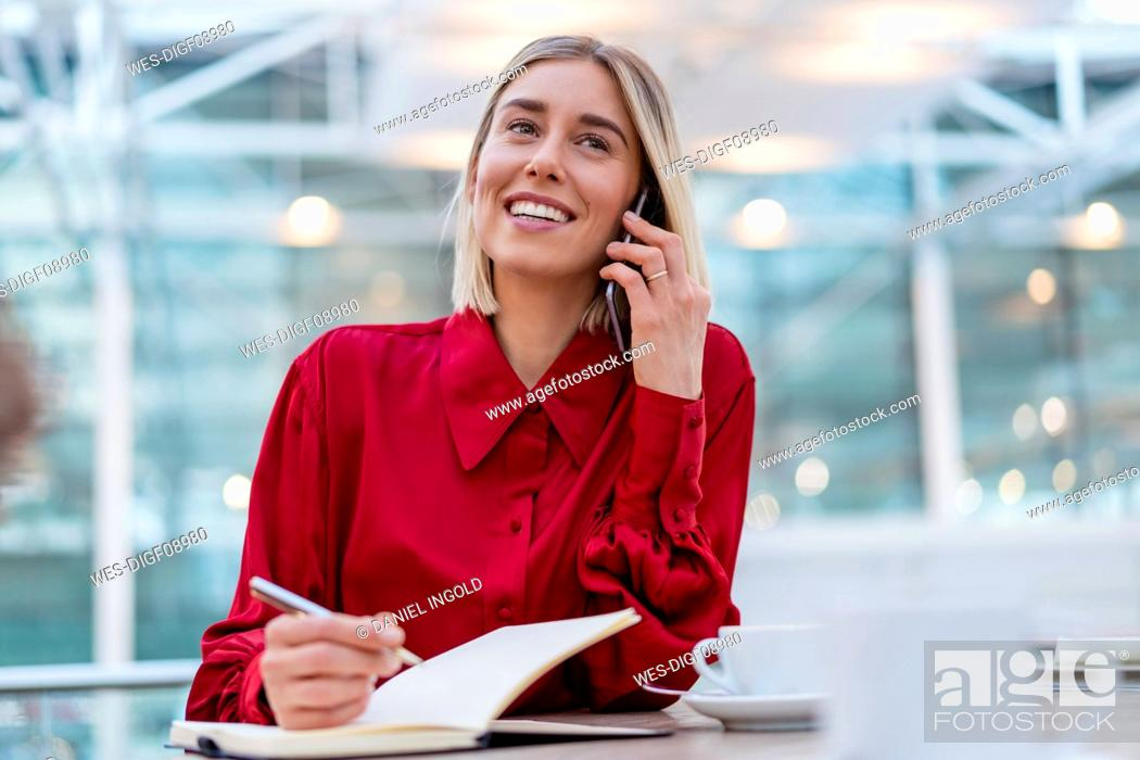 Stock Photo: Smiling young businesswoman with notebook on the phone.
