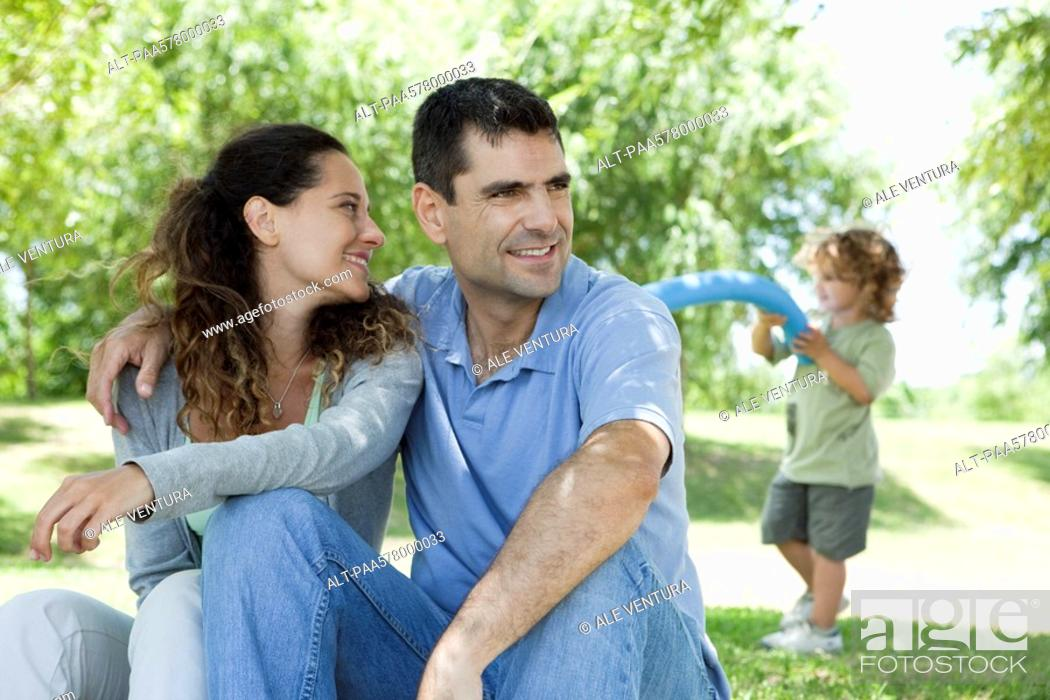 Stock Photo: Couple relaxing together outdoors, woman looking over shoulder at son playing in background.
