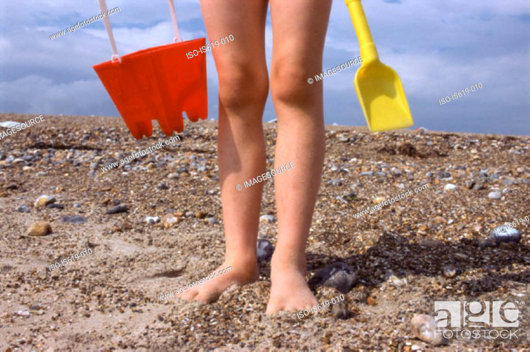 Stock Photo: Child on beach with bucket and spade.