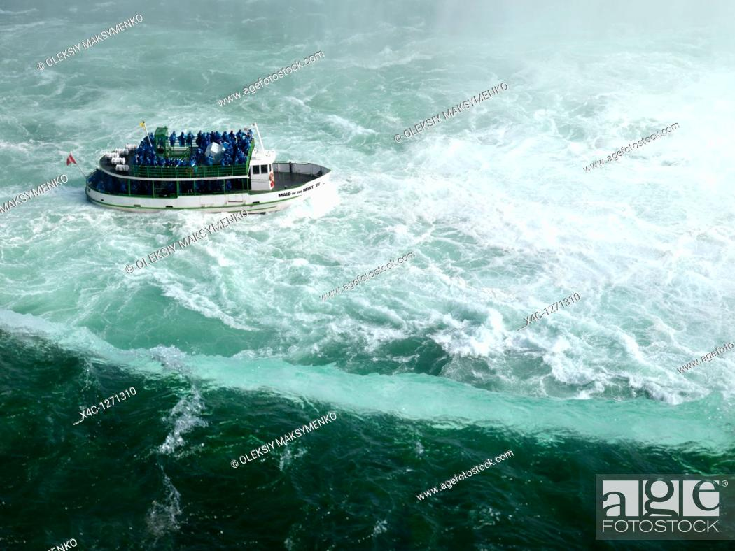 Stock Photo: People on Made of the Mist boat ride approaching Niagara Falls Horseshoe edge.