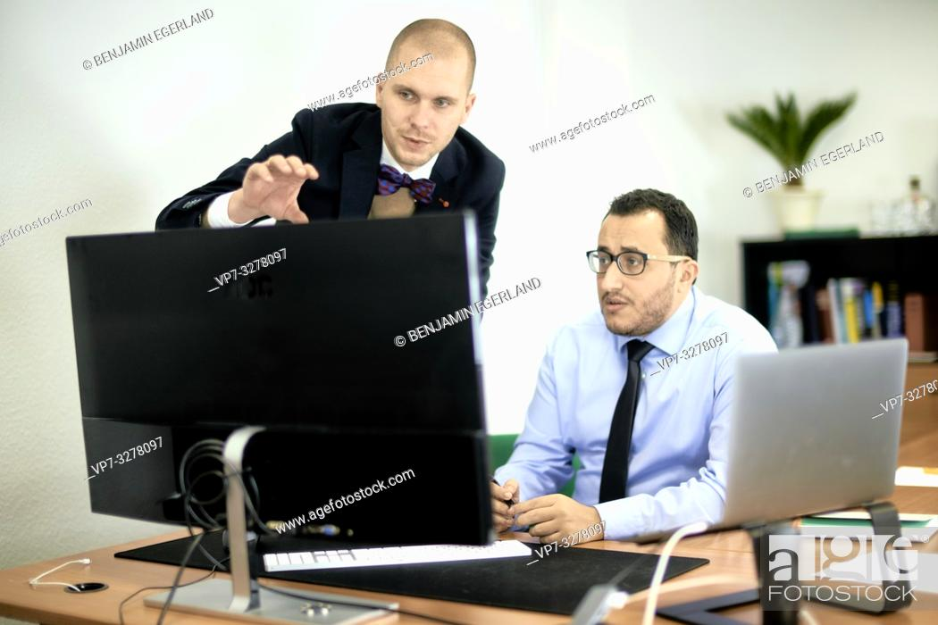 Imagen: business man teaching employee, manager explaining new concept at computer screen in office at work, in Cottbus, Brandenburg, Germany.
