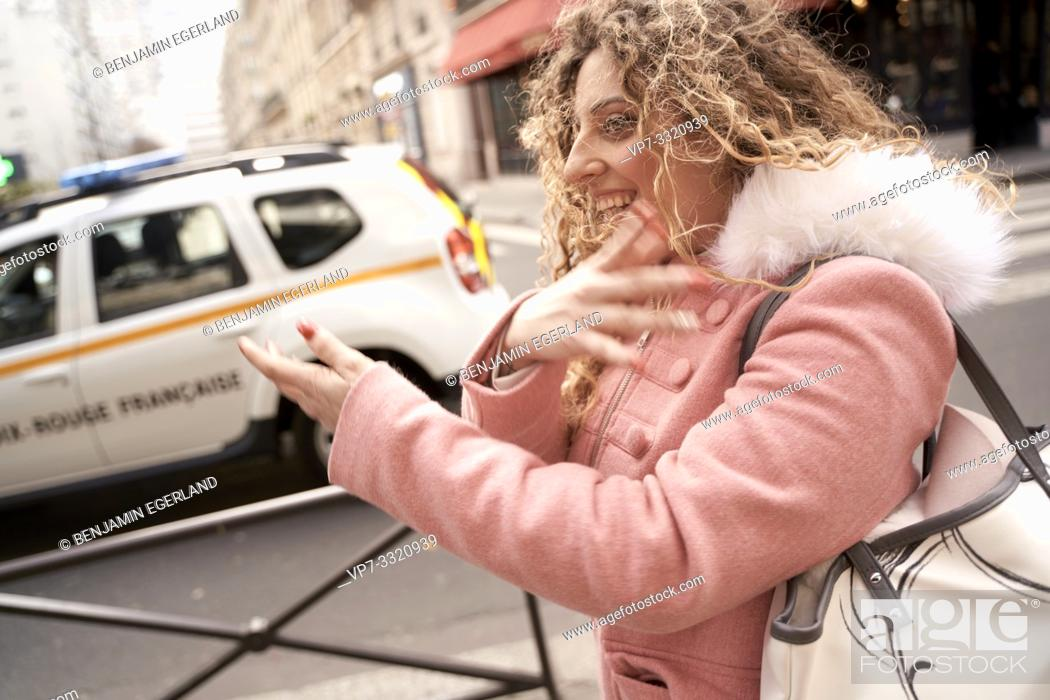 Imagen: woman moving arms at street in city, in Paris, France.