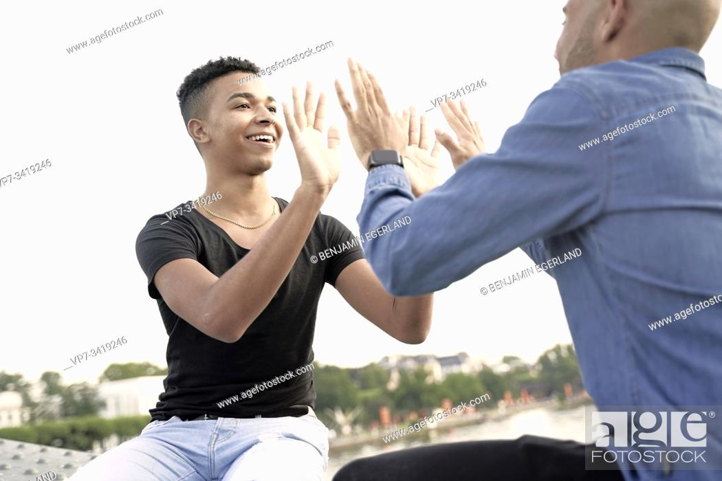 Stock Photo: Gay couple sitting on bridge structure, playing patty cake game. Frankfurt, Germany.