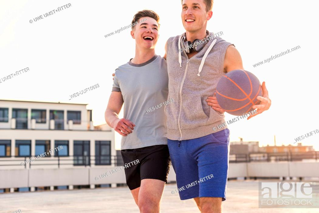 Stock Photo: Friends playing basketball at sunset on a rooftop.