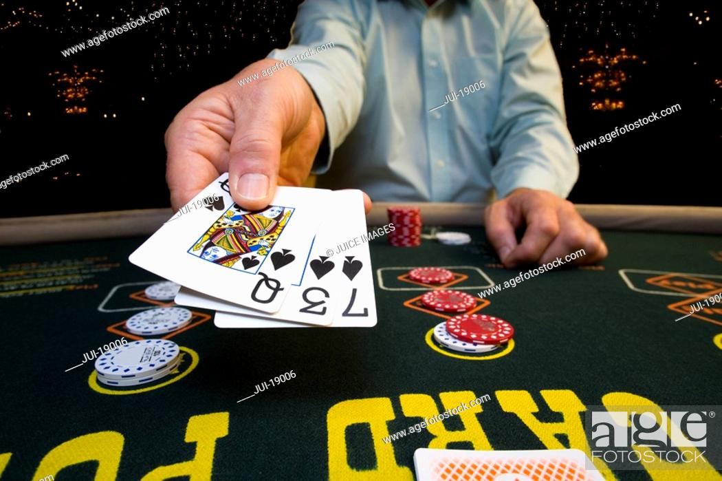 Stock Photo: Man gambling at poker table, holding out cards, mid section.