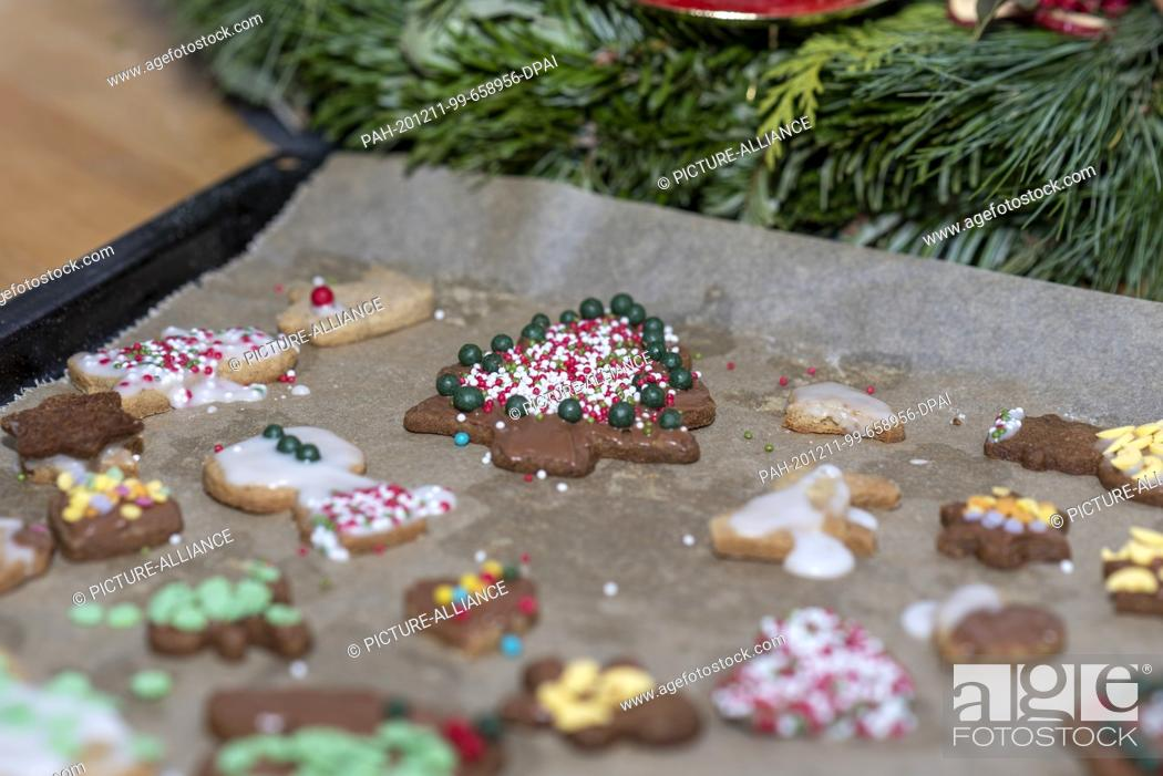 Stock Photo: 10 December 2020, Saxony-Anhalt, Magdeburg: A Christmas tree decorated with colourful sugar balls and chocolate lies on a tray next to other Christmas cookies.
