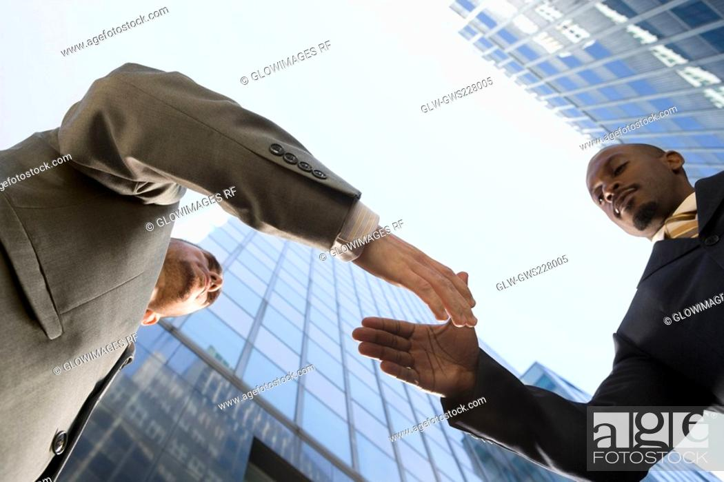 Stock Photo: Low angle view of two businessmen shaking hands.