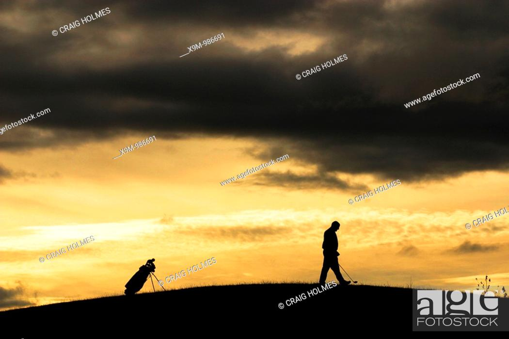 Stock Photo: Golfer at sunset, walking to his ball  Moody clouds rolling in during an atmospheric game of golf.