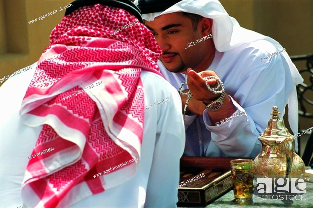 Photo de stock: Arab men enjoying tea and a game of backgammon.