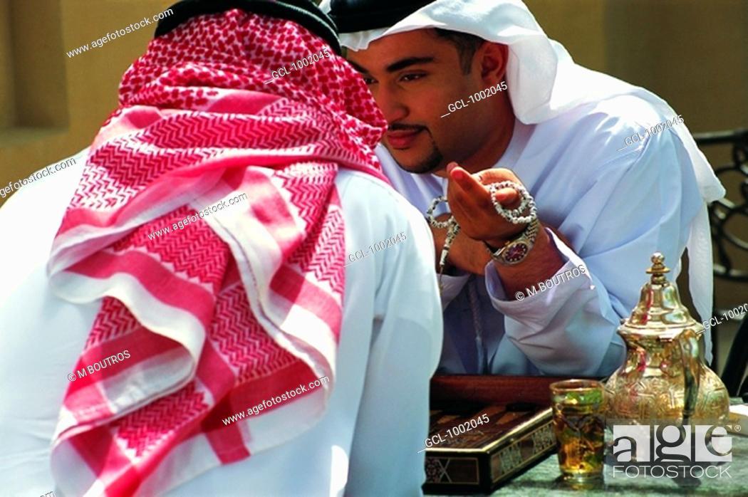 Stock Photo: Arab men enjoying tea and a game of backgammon.