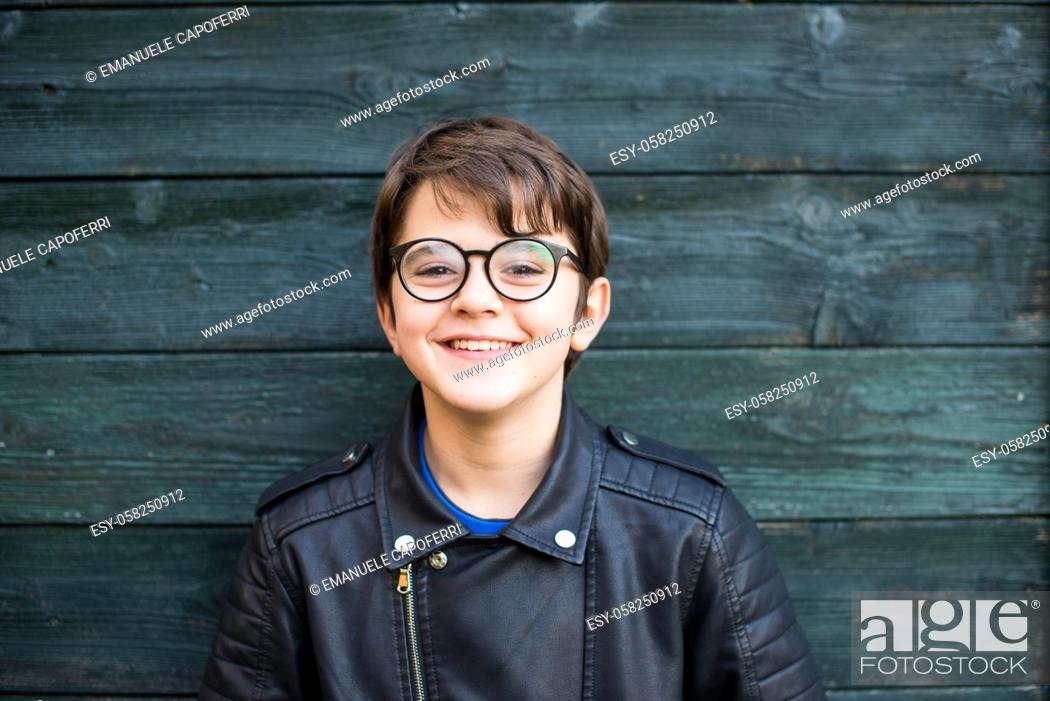Imagen: portrait of 12 year old boy with glasses smiling on green wood background dressed in leather jacket.
