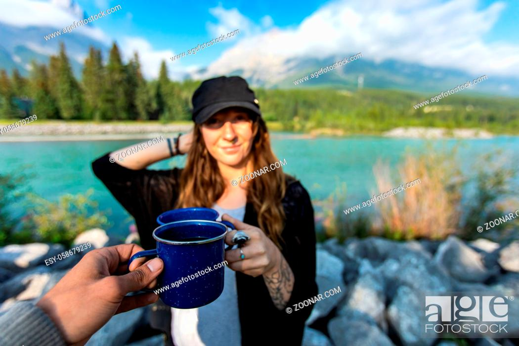 Stock Photo: Selective focus of two persons clinching their cups of coffee and tea together while standing in front of a nature scenery with a river.