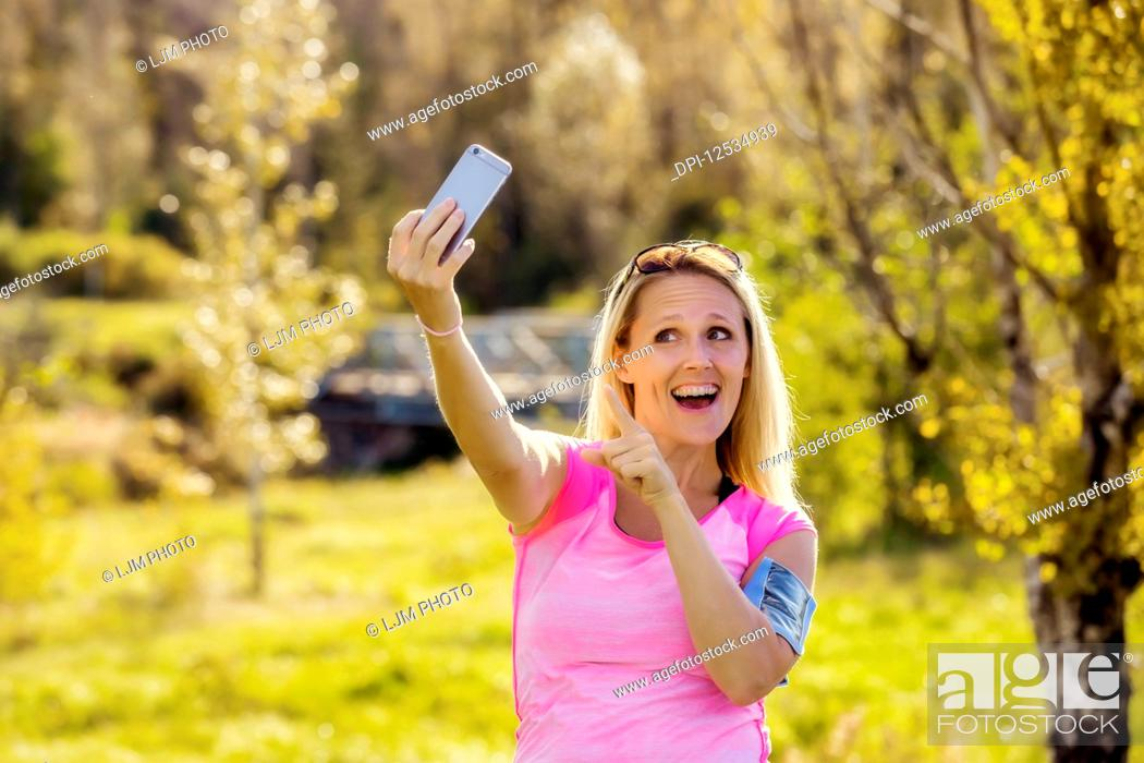 Stock Photo: A mature woman wearing active wear and an arm band to hold her smart phone takes a self-portrait before heading out for a run in a city park during the fall.