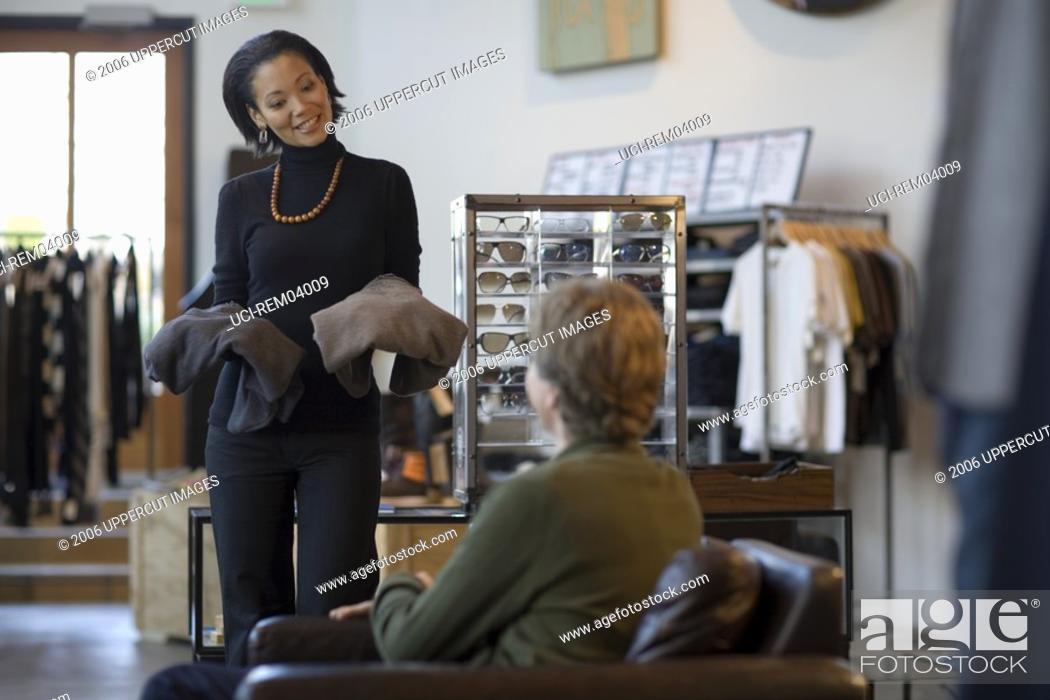 Imagen: Saleswoman showing man clothing.