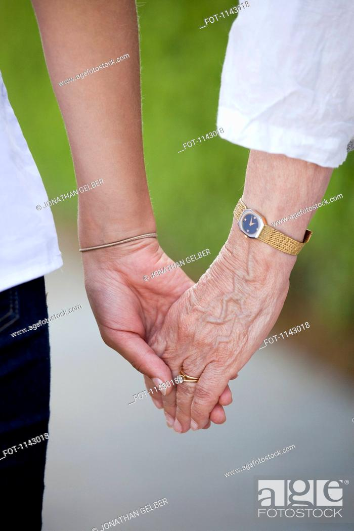 Stock Photo: Detail of a senior woman and a young woman holding hands.