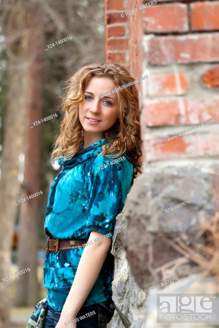 Stock Photo: A young woman standing by a brick building.