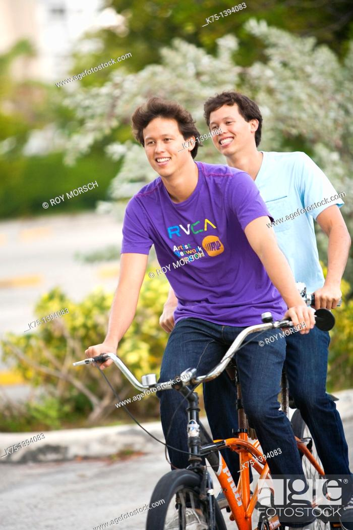 Stock Photo: Twins riding tandem bike.
