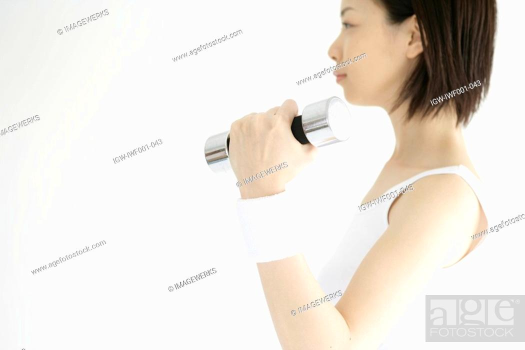 Stock Photo: Side view of a young woman lifting the dumbbell.