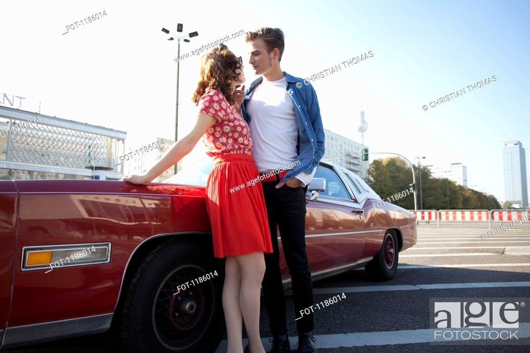 Stock Photo: A flirtatious rockabilly couple standing next to a vintage car, Berlin, Germany.