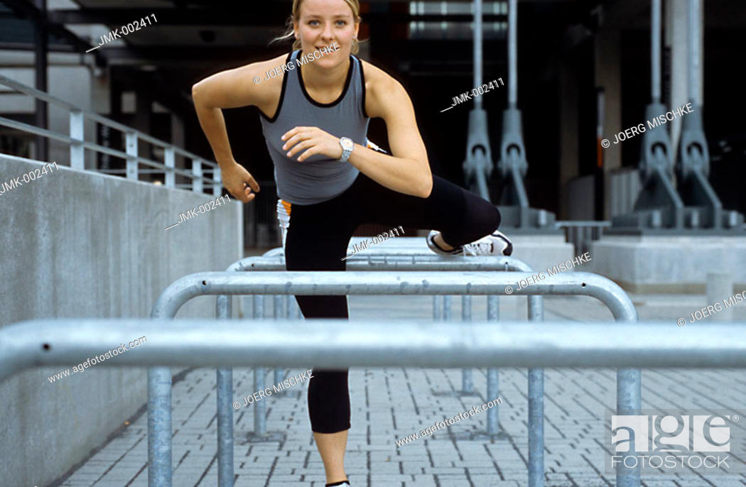Stock Photo: A young athletic woman, 15-20 20-25 25-30 years old, blond, sporty, overleaping a barrier.