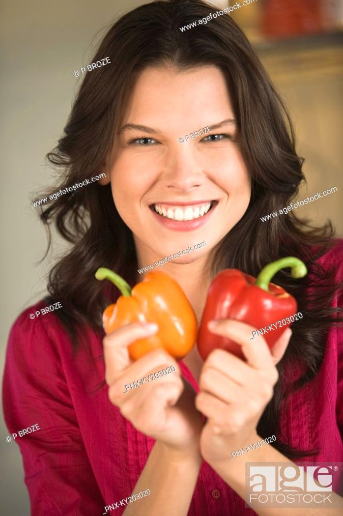 Stock Photo: Woman holding an orange and a red bell pepper.