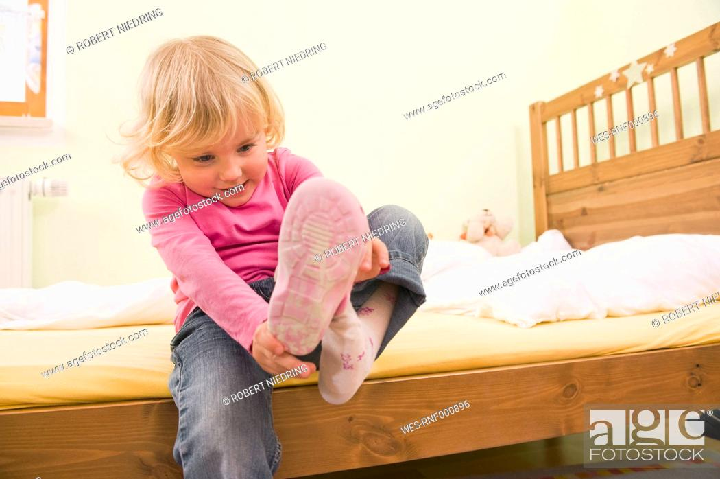 Stock Photo: Girl sitting on bed and putting shoes.