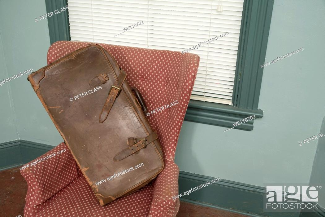 Photo de stock: Old suitcase on a chair.