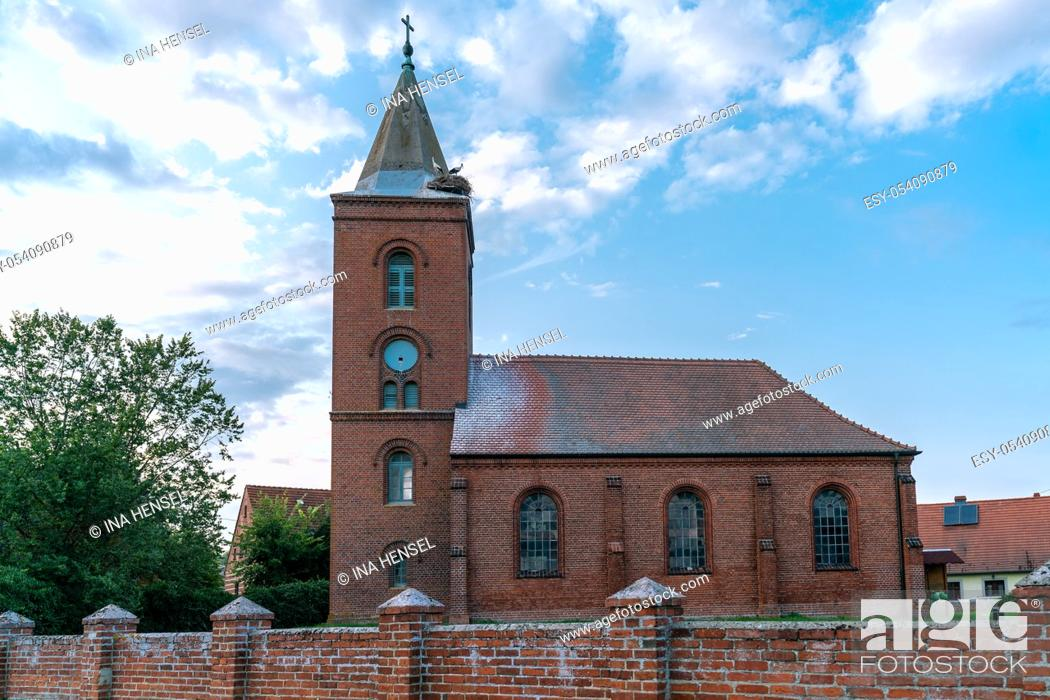 Stock Photo: Church in Guelpe, Germany with two storks breeding on the clock tower roof.