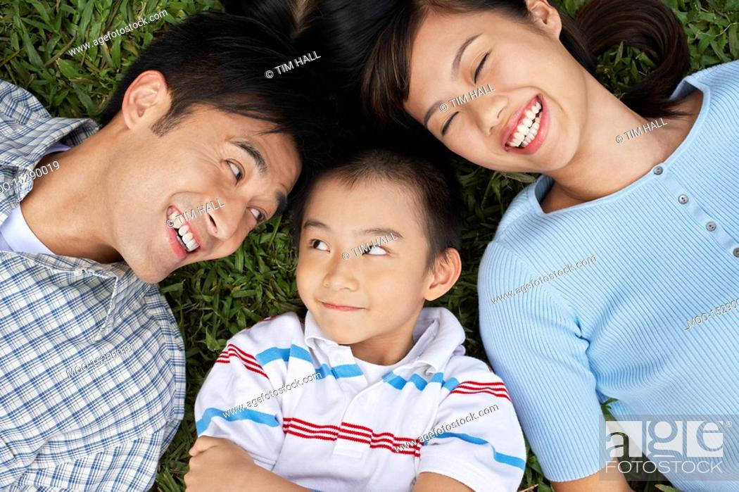 Stock Photo: Couple with son 7-9 lying on grass portrait elevated view.