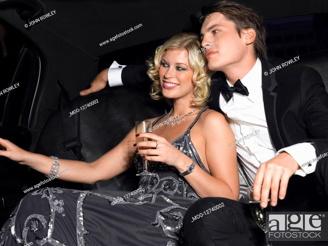 Stock Photo: Couple in back of car drinking champagne looking away.