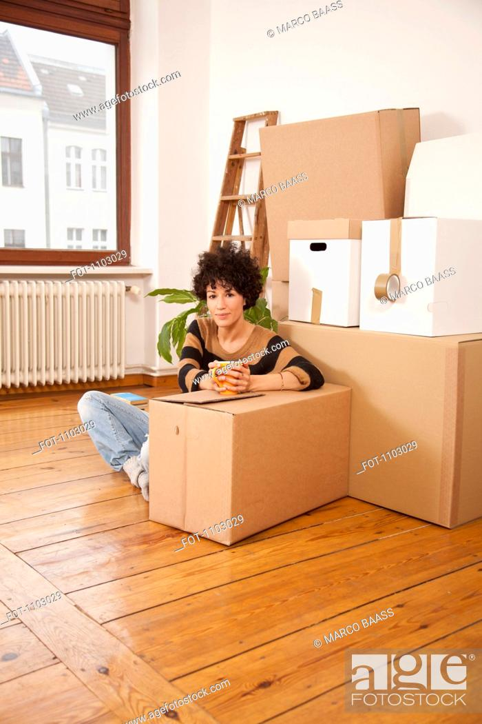 Stock Photo: A serious woman taking a coffee break while moving house.