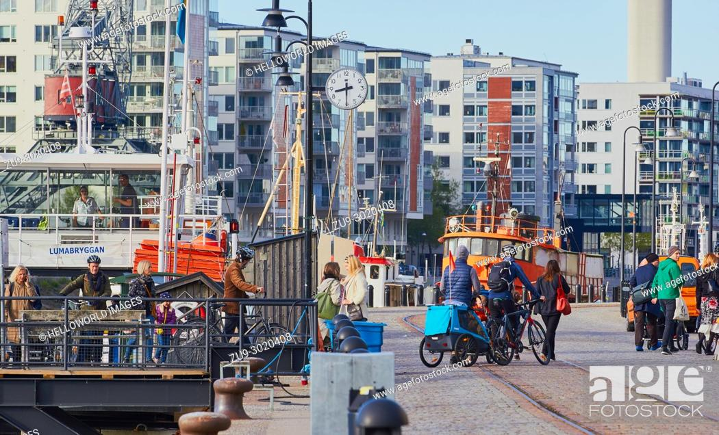 Stock Photo: Variety of different passengers getting off ferry, Hammarby Sjostad eco neighbourhood a pioneer in sustainable development, Hammarby Lake, Stockholm, Sweden.