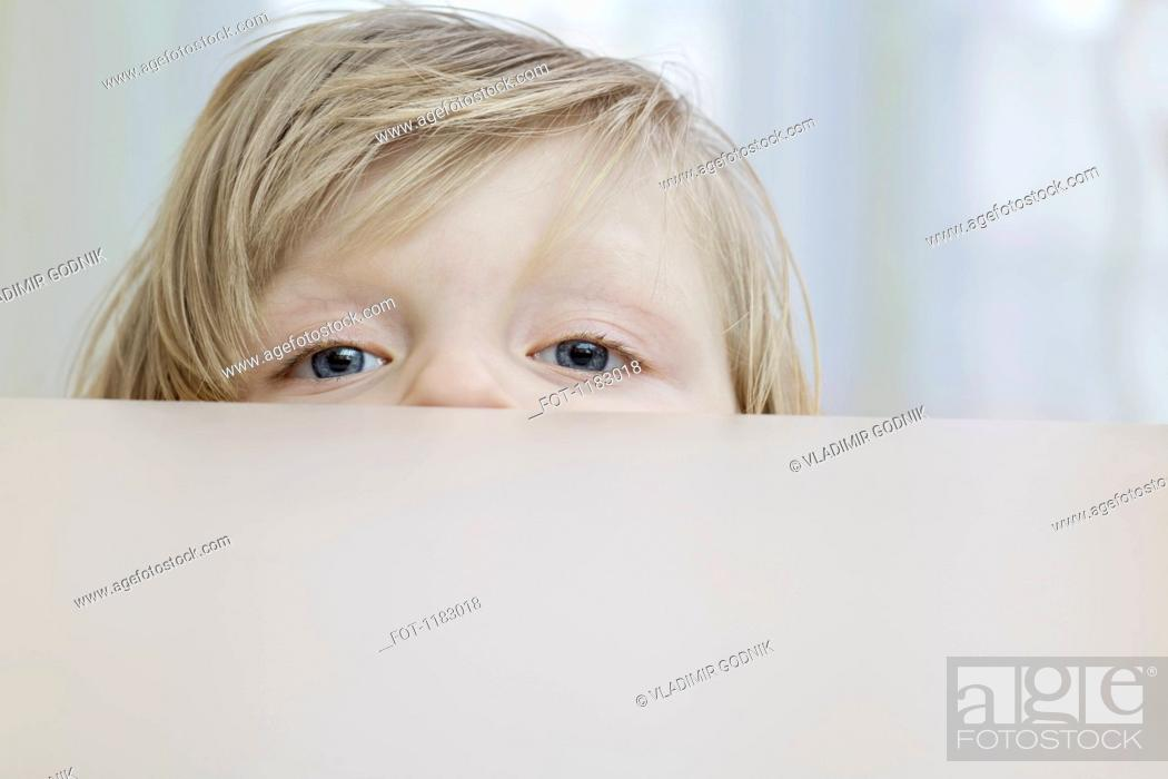 Stock Photo: A little girl peeking over a table.