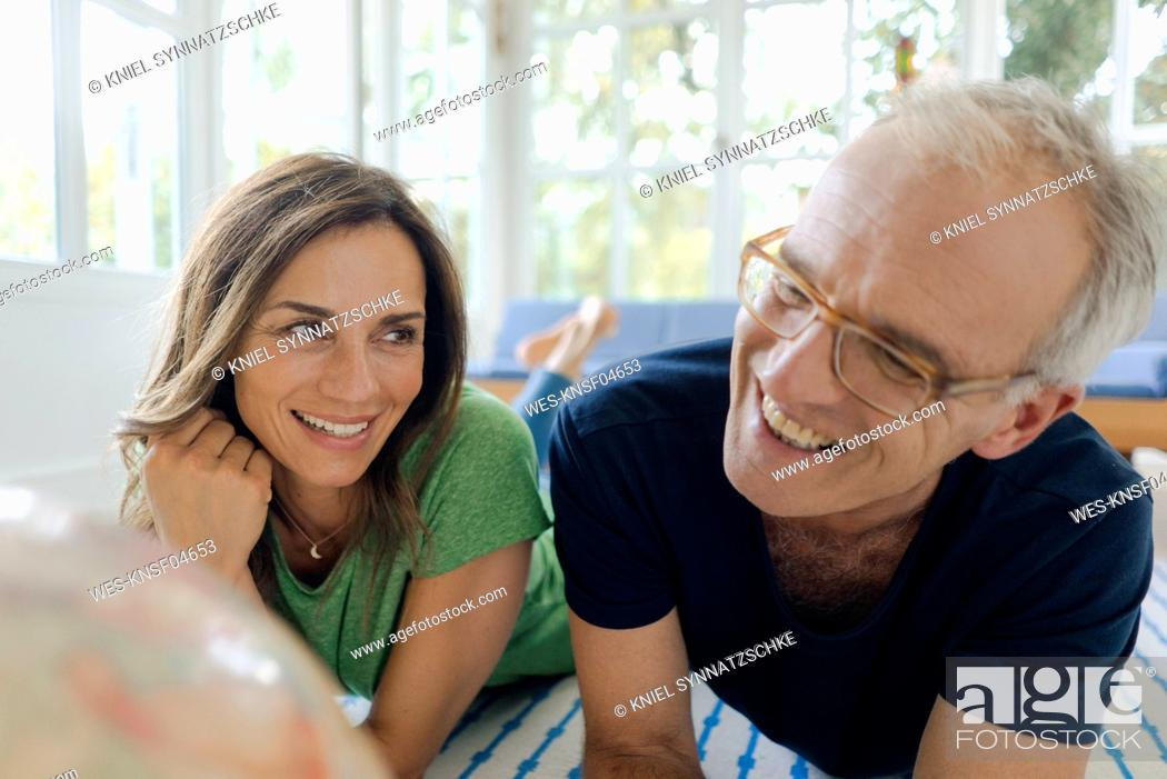 Stock Photo: Happy mature couple lying on the floor at home looking at globe.