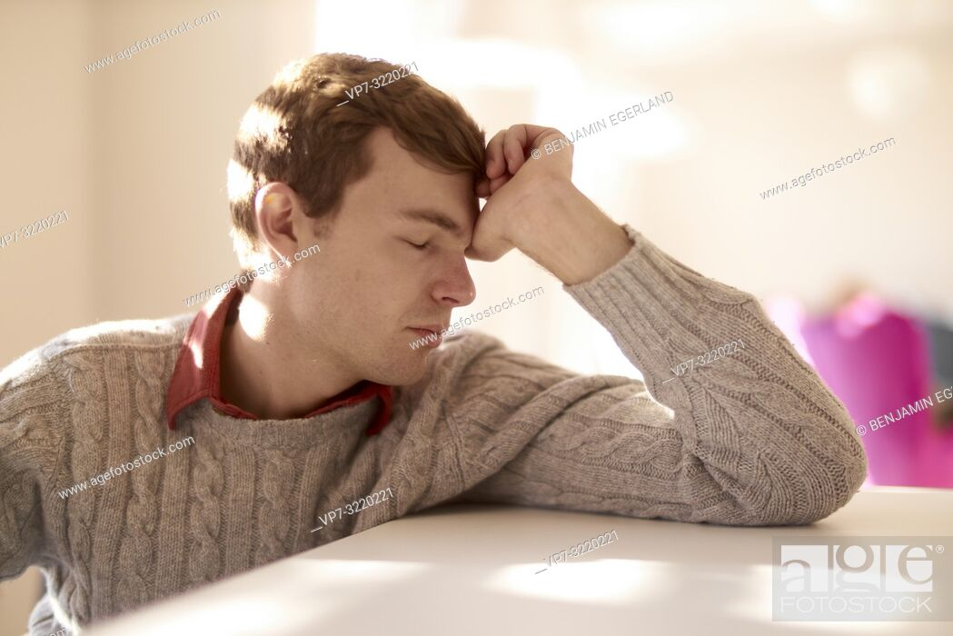 Stock Photo: Young man at table with closed eyes, indoors, student, business man, office.