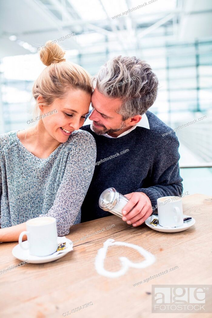 Stock Photo: Couple sitting together, drinking coffee, heart shape made from sugar on table in front of them.
