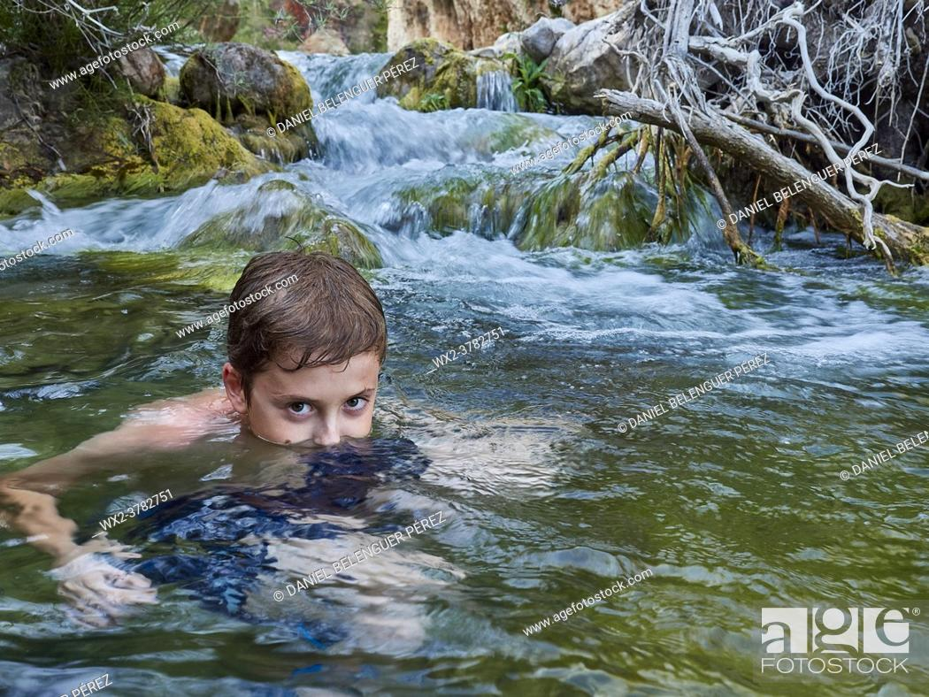 Stock Photo: Boy looking at camera while is sumerged on a mountain river. Villahermosa river, Ludiente, Castellón, Spain.