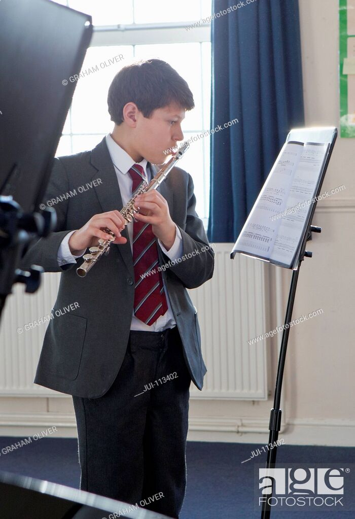 Stock Photo: Middle school student playing flute with sheet music in music class.