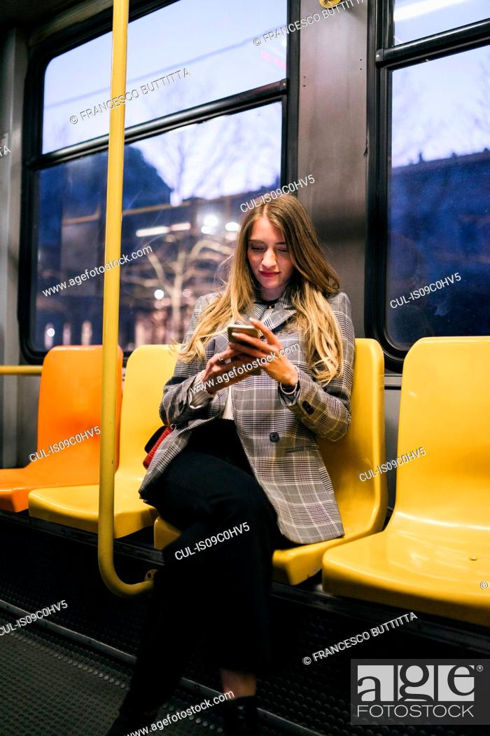 Stock Photo: Young woman with long blond hair sitting in train carriage looking at smartphone at dusk.